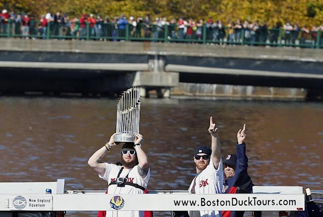 Boston Red Sox's Jarrod Saltalamacchia, left, holds the World Series trophy as Ryan Dempster, center, raises his arm from a duck boat on the Charles River during a rolling victory parade celebrating the team's World Series title Saturday, Nov. 2, 2013, in Boston. (AP Photo/Michael Dwyer)