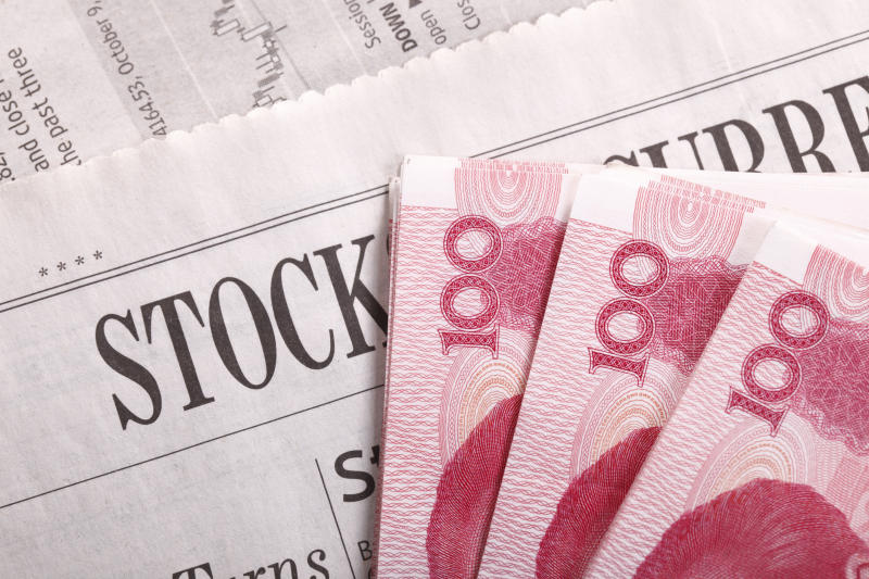 Chinese yuan notes laid out atop a newspaper's stock markets section.