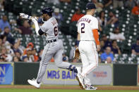 Detroit Tigers' Akil Baddoo, left, points to the stands as he crosses Houston Astros third baseman Alex Bregman, right, as he rounds the bases on his home run during the third inning of a baseball game Monday, April 12, 2021, in Houston. (AP Photo/Michael Wyke)