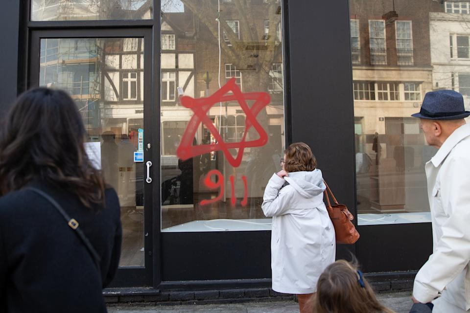 Anti-semitic graffiti in the form of numbers, 9 11, and a Star of David, on a shop window in Belsize Park, North London.