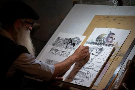 Michael Netzer, an American comics artist formerly named Mike Nasser, sketches at his attic studio in his home in the Jewish settlement of Ofra in the Israeli-occupied West Bank