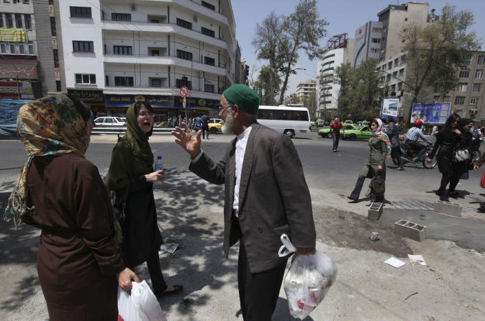 An Iranian elderly man, a supporter of the presidential candidate Hasan Rowhani, talks with two women on a street of Tehran, Iran, a day after the election, Saturday, June 15, 2013. Iran's reformist-backed presidential candidate surged to a wide lead in early vote counting Saturday, a top official said, suggesting a flurry of late support could have swayed a race that once appeared solidly in the hands of Tehran's ruling clerics. The strong margin for former nuclear negotiator Rowhani may be enough to give him an outright victory and avoid a two-person runoff next Friday. (AP Photo/Vahid Salemi)