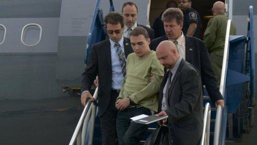 Luka Rocco Magnotta is escorted off an airplane by police as he arrives in Montreal on Monday