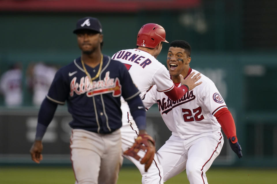 Washington Nationals' Juan Soto (22) and Trea Turner celebrate in front of Atlanta Braves second baseman Ozzie Albies after Soto hit a game-winning single in the ninth inning of an opening day baseball game at Nationals Park, Tuesday, April 6, 2021, in Washington. Victor Robles scored on the play, and Washington won 6-5. (AP Photo/Alex Brandon)