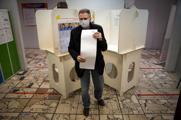 A man walks to casts his ballot at a polling station during Parliamentary elections in Moscow, Russia, Friday, Sept. 17, 2021. Russia has begun three days of voting for a new parliament that is unlikely to change the country's political complexion. There's no expectation that United Russia, the party devoted to President Vladimir Putin, will lose its dominance in the State Duma. (AP Photo/Alexander Zemlianichenko)