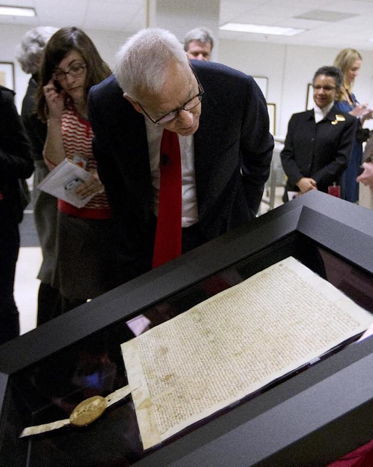 Carlyle Group co-founder and owner of Magna Carta David Rubenstein looks at the 1297 Magna Carta in its new state-of-the-art encasement, Thursday, Feb. 2, 2012, at the National Archives in Washington. (AP Photo/Manuel Balce Ceneta)