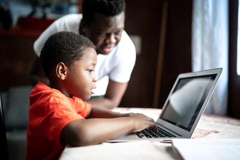 Father and son studying with laptop on an online class at home
