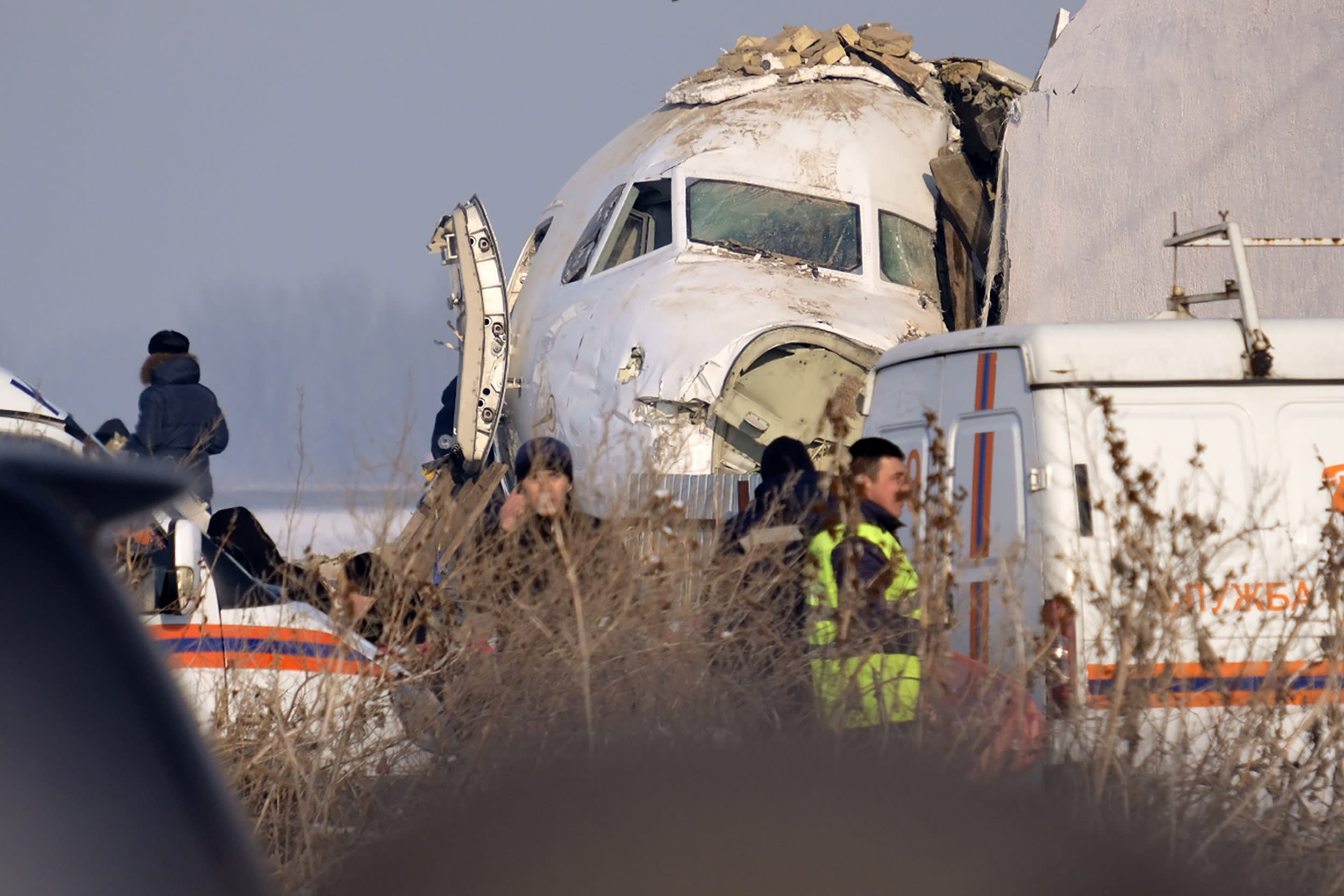 Police stand guard as rescuers assist on the site of a plane crashed near Almaty International Airport, outside Almaty, Kazakhstan, Friday, Dec. 27, 2019. The Kazakhstan plane with 98 people aboard crashed shortly after takeoff early Friday. (AP Photo/Vladimir Tretyakov)