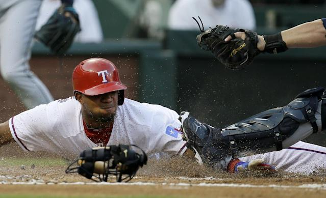 Texas Rangers' Elvis Andrus is blocked from touching the plate by Seattle Mariners' Humberto Quintero while Andrus was trying to score on a single by Adrian Beltre in the first inning of a baseball game, Friday, Aug. 16, 2013, in Arlington, Texas. Andrus was out on the play. (AP Photo/Tony Gutierrez)