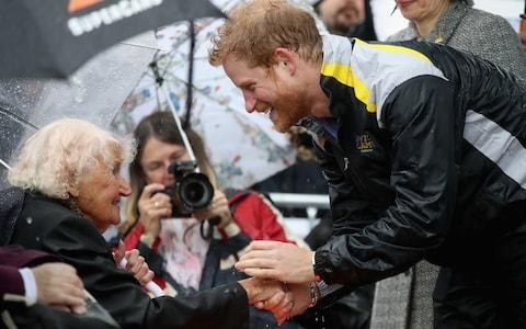 Prince Harry greets Daphne Dunne during a walkabout in the torrential rain ahead of a Sydney 2018 Invictus Games Launch Event, in June 2017 - Credit: Chris Jackson/Getty Images