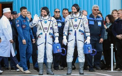 Alexei Ovchinin and Nick Hague wave to onlookers before boarding the spacecraft - Credit: Sergei Savostyanov/TASS/Barcroft