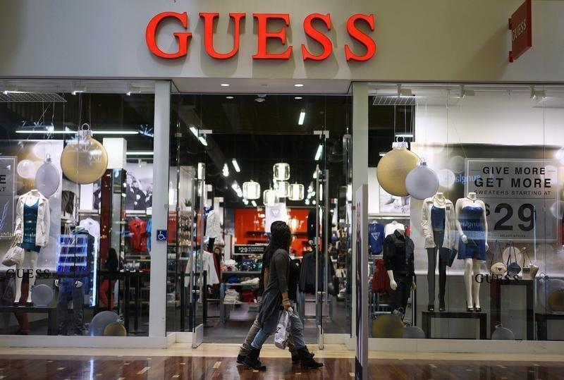 Shoppers walk by a Guess? store in Golden