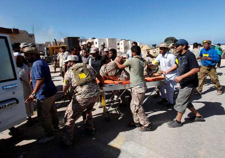 A wounded fighter of Libyan forces allied with the U.N.-backed government is evacuated on a stretcher by his comrades at the eastern frontline of fighting with Islamic State militants, in Sirte, Libya, October 20, 2016. REUTERS/Ismail Zitouny