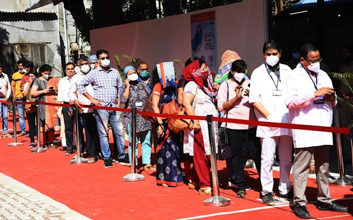 Indian Health workers wait in line to receive a coronavirus vaccine in Mumbai - Anadolu