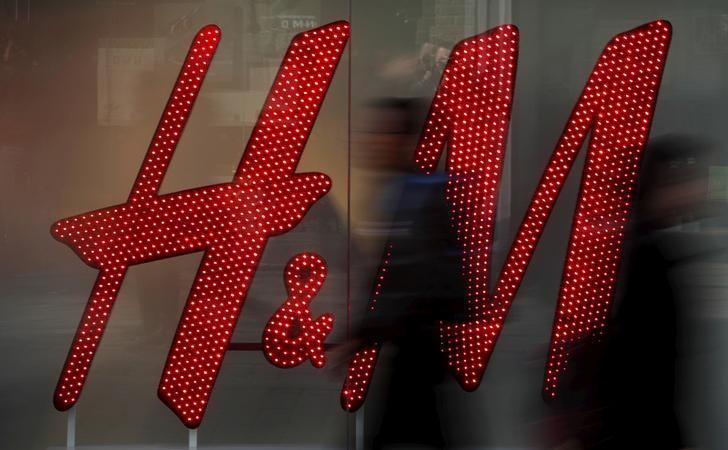 People walk past a company logo in the window of a H&M store in Manchester