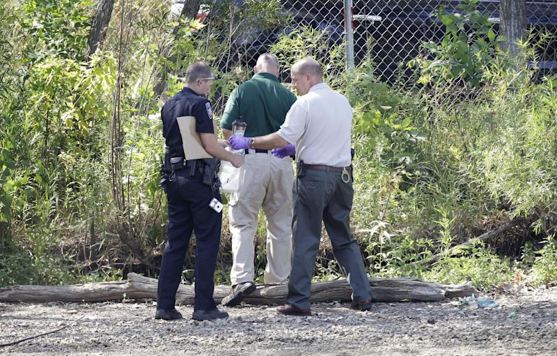 Law enforcement authorities collect possible evidence near Meyers Lake where Lyric Cook-Morrissey, 10, and Elizabeth Collins, 8, disappeared last Friday, Tuesday, July 17, 2012, in Evansdale, Iowa. The girls' bikes were found Friday afternoon near a bike trail at the edge of the lake. (AP Photo/Charlie Neibergall)