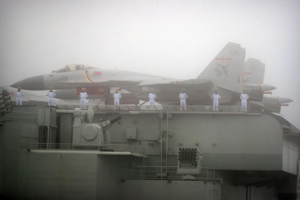 FILE - In this April 23, 2019, file photo, sailors stand near fighter jets on the deck of the Chinese People's Liberation Army (PLA) Navy aircraft carrier Liaoning as it participates in a naval parade in the sea near Qingdao in eastern China's Shandong province. China says its first entirely homebuilt aircraft carrier, yet to be named, has transited the Taiwan Strait on its way to the South China Sea for exercises. (AP Photo/Mark Schiefelbein, Pool)