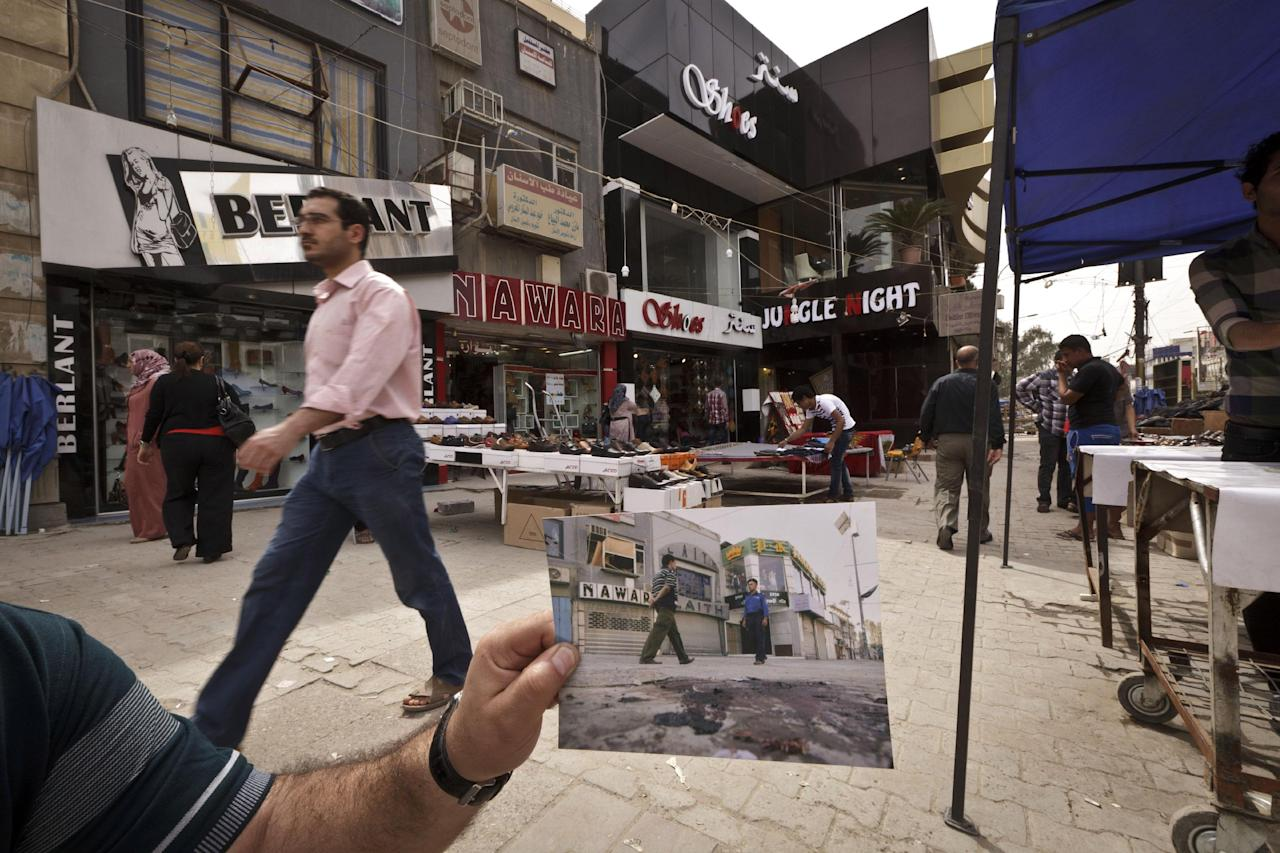 In this Saturday, March 16, 2013 photo, shoppers walk in Baghdad's busy shopping district of Karrada, at the same site of an Associated Press photo taken by Hadi Mizban on Monday, Sept. 29, 2008 after a bombing that killed 22 people. Bloody attacks launched by terrorists who thrived in the post-invasion chaos are painfully still frequent, albeit less so than a few years back, and sectarian and ethnic rivalries are again tearing at the fabric of national unity. (AP Photo/Maya Alleruzzo)