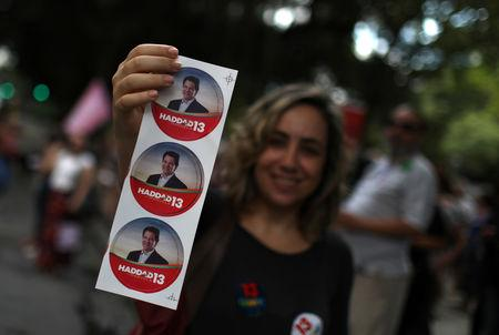 A supporter of presidential candidate Fernando Haddad holds stickers during a demonstration in Rio de Janeiro, Brazil October 27, 2018. REUTERS/Pilar Olivares