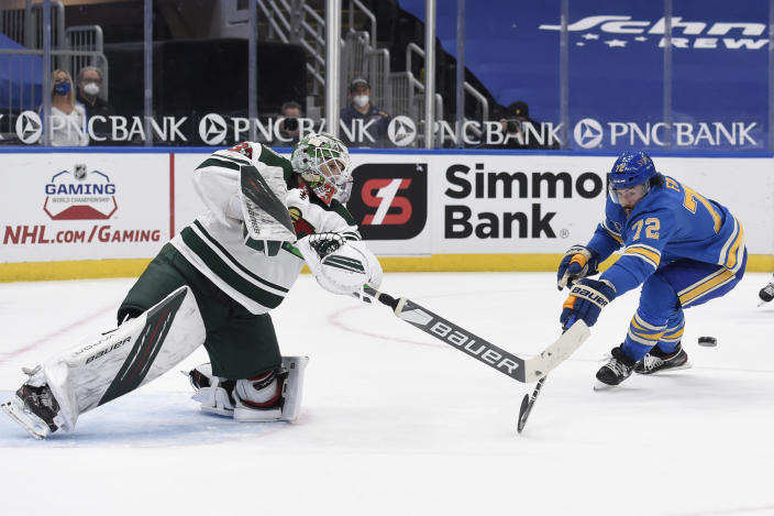 St. Louis Blues' Justin Faulk (72) attempts to block a pass from Minnesota Wild's Cam Talbot (33) during overtime of an NHL hockey game on Saturday, April 10, 2021, in St. Louis. (AP Photo/Joe Puetz)