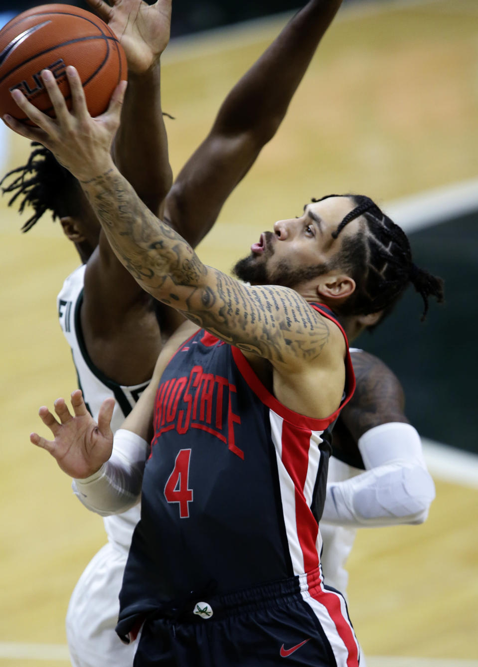 Ohio State guard Duane Washington Jr. (4) goes to the basket against Michigan State during the first half of an NCAA college basketball game Thursday, Feb. 25, 2021, in East Lansing, Mich. (AP Photo/Duane Burleson)