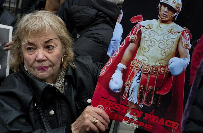 "A woman holds a sign honoring Hector ""Macho"" Camacho outside St. Cecilia's Roman Catholic Church in New York after Camacho's funeral, Saturday, Dec. 1, 2012. Doctors pronounced Camacho dead on Saturday, Nov. 24, after he was removed from life support at his family's direction. He never regained consciousness after at least one gunman crept up to his car in a darkened parking lot in Puerto Rico and opened fire. (AP Photo/Craig Ruttle)"