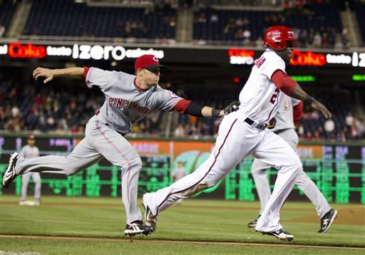 Cincinnati Reds shortstop Zack Cozart, left, tags out Washington Nationals Roger Bernadina during the 12th inning of a baseball game on Friday, April 13, 2012, in Washington. The Nationals won 2-1 in thirteen innings. (AP Photo/Evan Vucci)