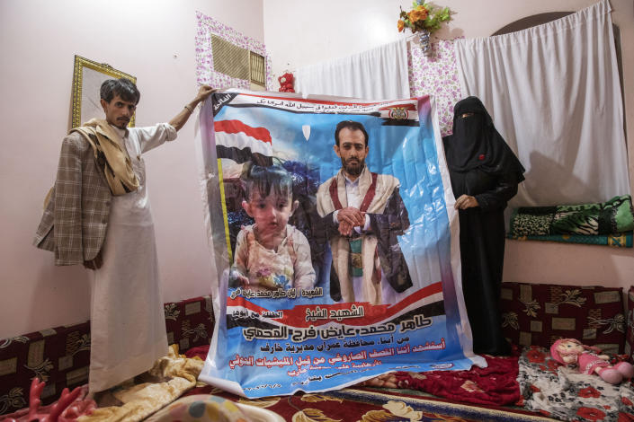 Gamila Salih Ali, right, and Ahmed Farag, mother and uncle of two-year-old Liyan Taher, seen in poster at left, who was killed with her father 32-year-old Taher Farag, seen in poster at right, in a ballistic missile and an explosive-laden drone fired by Yemen's Houthi rebels that hit a fuel station on June 5, 2021 in Rawdha neighborhood, show a poster with photos of them at their home in Marib, Yemen, Saturday, June 19, 2021. (AP Photo/Nariman El-Mofty)