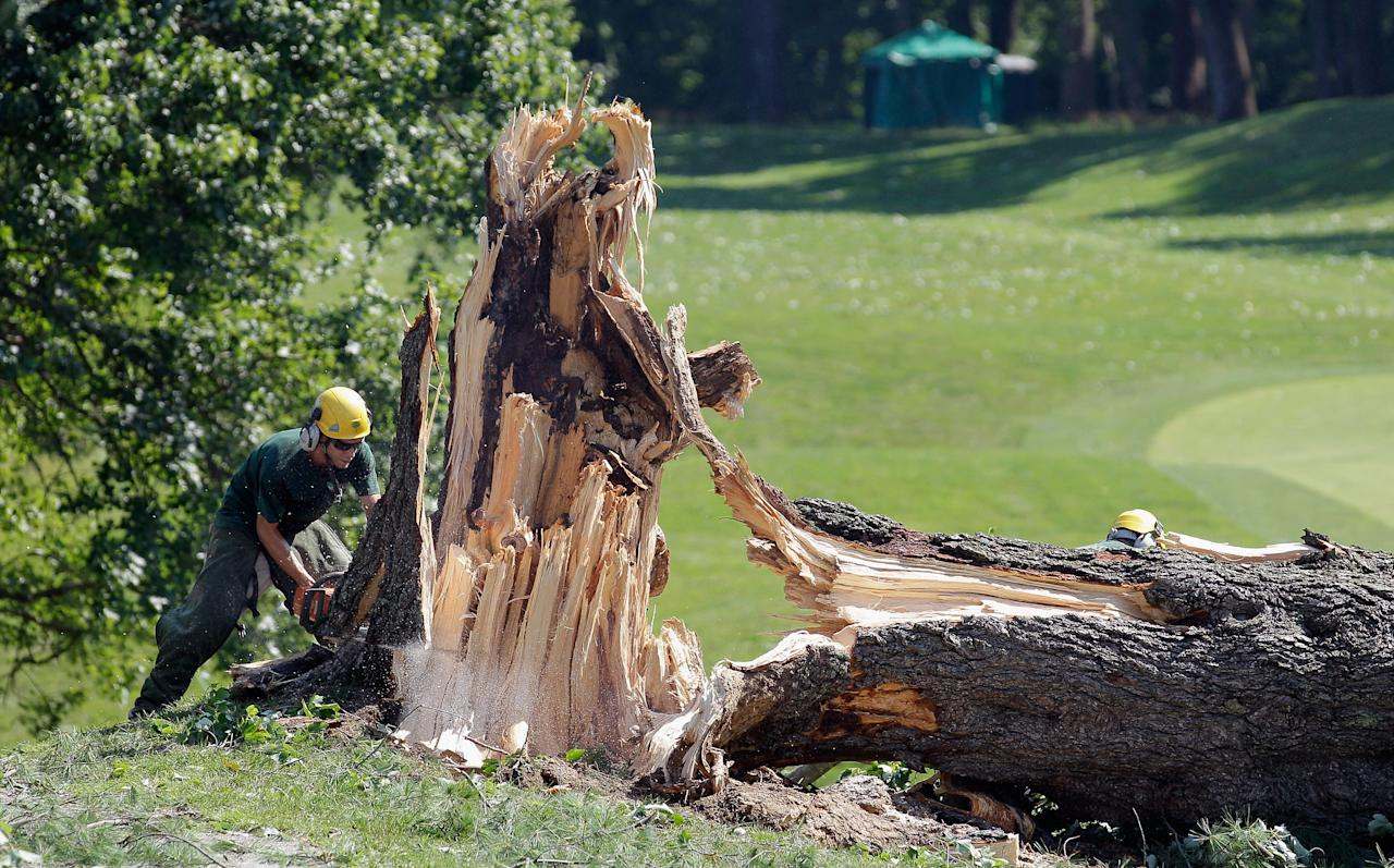 BETHESDA, MD - JUNE 30:  Workers cut up a tree along the 14th fairway from overnight storm damage that delayed the start of Round Three of the AT&T National at Congressional Country Club on June 30, 2012 in Bethesda, Maryland. Overnight storms knocked out power to up to a million people in the D.C. area and course officials have  closed the course to spectators. (Photo by Rob Carr/Getty Images)