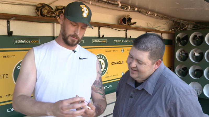 John Axford opens 1992 Topps cards in the A's dugout. (Yahoo Sports)