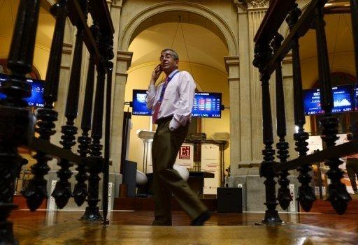 A trader speaks on his mobile phone next to the IBEX-35 index billboard at Madrid's stock exchange