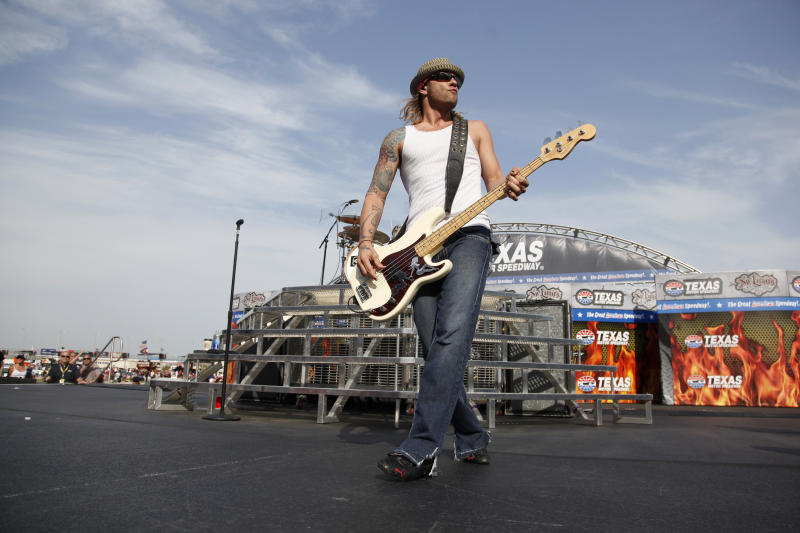FILE - In this April 9, 2011 file photo, 3 Doors Down' bassist Todd Harrell performs before a NASCAR auto race at Texas Motor Speedway in Fort Worth, Texas. Police say Harrell has been charged with vehicular homicide by intoxication after an interstate crash left another motorist dead in the Nashville area. (AP Photo/Tim Sharp, File)