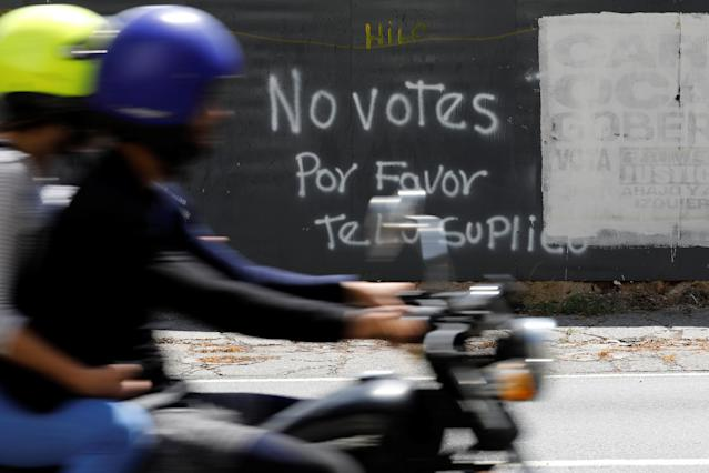 "A motorcycle passes graffiti painted on a fence in Caracas, Venezuela May 12, 2018. Graffiti reads: ""Do not vote, please I beg you"". Picture taken on May 12, 2018. REUTERS/Carlos Jasso"