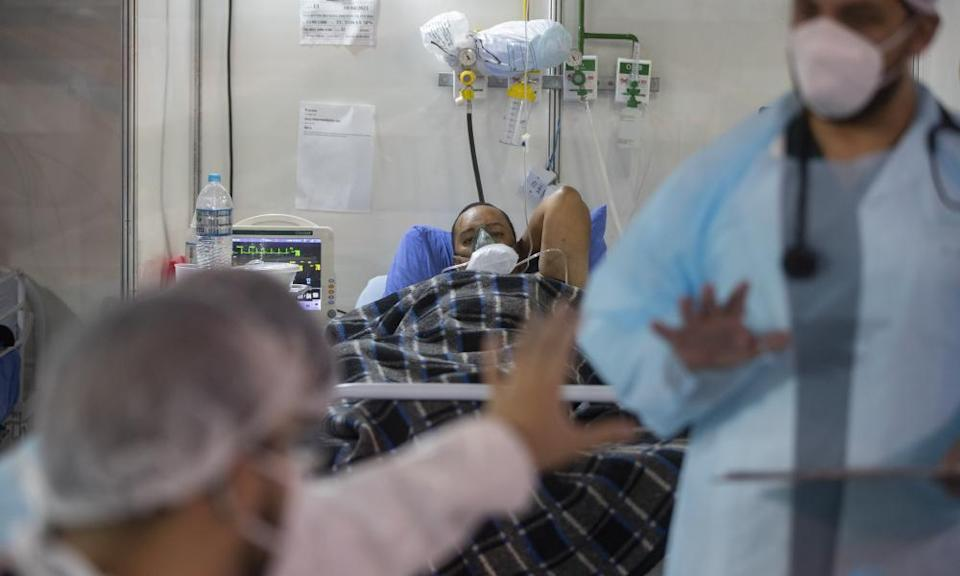 Everton Nascimento de Oliveira, 32, lies in an emergency unit bed of a field hospital in Ribeirao Pires.