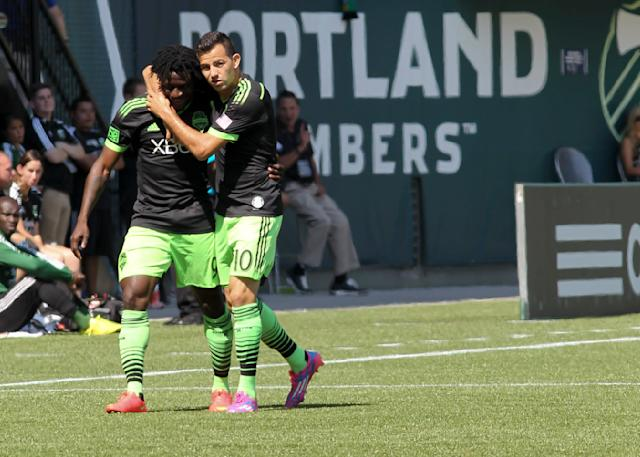 Seattle Sounders' Obafemi Martins, left, is congratulated by teammate Marco Paapa after scoring a goal against the Portland Timbers during an MLS soccer game in Portland, Ore., Sunday, Aug. 24, 2014. (AP Photo/Natalie Behring)