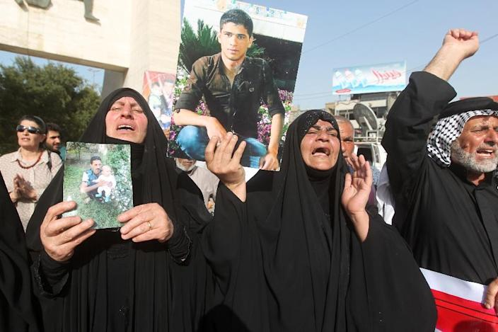 Iraqi women hold pictures of their relatives -- who are believed to have been killed in the Speicher massacre -- during a demonstration in Baghdad, on April 27, 2015 (AFP Photo/Ahmad al-Rubaye)
