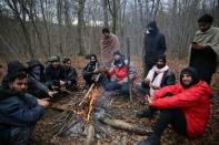 "Migrants try to warm themselves near the burned migrant center ""Lipa"" in Bihac"