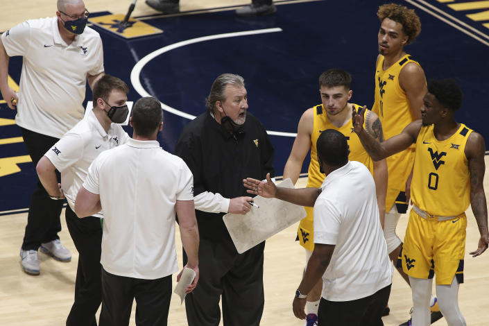 West Virginia coach Bob Huggins speaks with players during the first half of an NCAA college basketball game Saturday, Jan. 30, 2021, in Morgantown, W.Va. (AP Photo/Kathleen Batten)