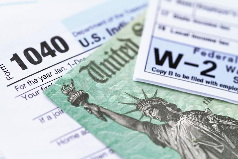 1040 income tax form and w-2 wage statement with a federal Treasury refund check. Closeup with selective focusing.