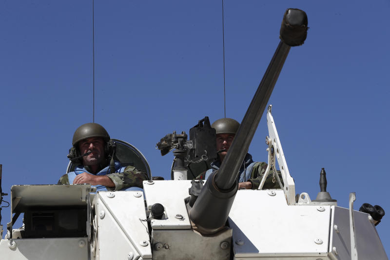 Irish UN peacekeepers sit on their armored personnel carrier as they patrol near the fields that burned on Sunday by the Israeli army shells in the southern Lebanese-Israeli border village of Maroun el-Ras, Lebanon, Monday, Sept. 2, 2019. The Lebanon-Israel border was mostly calm with U.N. peacekeepers patrolling the border Monday, a day after the Lebanese militant Hezbollah group fired a barrage of anti-tank missiles into Israel, triggering Israeli artillery fire that lasted less than two hours and caused some fires. (AP Photo/Hussein Malla)