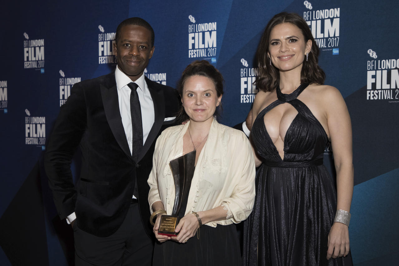 Documentary competition winner Lucy Cohen, centre, holds her Grieson award for her film 'Kingdom of Us' as she poses with actors Adrien Lester, left, and Hayley Atwell at the London Film Festival Awards in London, Saturday, Oct. 14, 2017. (Photo by Vianney Le Caer/Invision/AP)