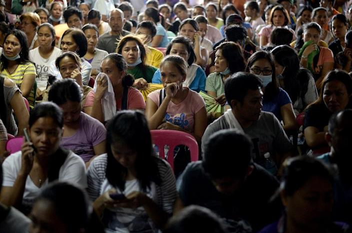 Relatives of the victims killed in a fire that gutted a footwear factory the day before attend a briefing from local government officials at a makeshift morgue in suburban Manila on May 14, 2015 (AFP Photo/Noel Celis)