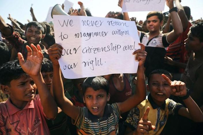 A boy holds a placard as hundreds of Rohingya refugees protest against their repatriation at the Unchiprang camp in Teknaf