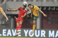 Oman's Abdulaziz Al-Muqbali, left , fights for the ball with Australia's Trent Sainsbury during a FIFA World Cup group B qualifying soccer match between Australia and Oman in Doha, Qatar, Thursday, Oct. 7, 2021. (AP Photo/Hussein Sayed)