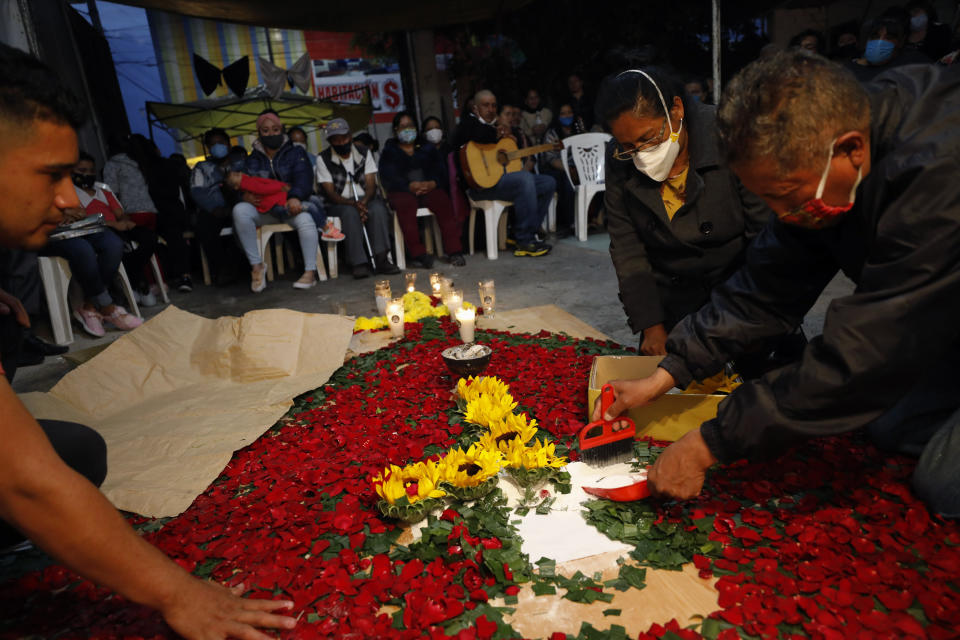 Family members carefully collect sunflowers, petals to be buried atop the grave of Luz Maria Gonzalez, during her cross raising ceremony in the family home in Valle de Chalco, on the outskirts of Mexico City, Friday, July 3, 2020. Gonzalez, 56, who had long suffered from asthma, diabetes, and hypertension, died two days after her 29-year-old son, who was hospitalized for breathing problems and a cough before dying of complications said to be related to pneumonia and undiagnosed diabetes. (AP Photo/Rebecca Blackwell)