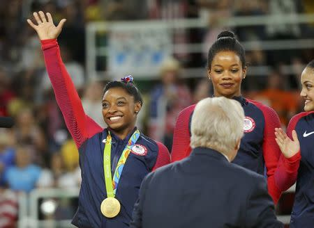 2016 Rio Olympics - Artistic Gymnastics - Women's Team Victory Ceremony - Rio Olympic Arena - Rio de Janeiro, Brazil - 09/08/2016. Simone Biles (USA) of USA (L) waves on the podium with her gold medal, next to team mates Gabrielle Douglas (USA) of USA (Gabby Douglas) and Laurie Hernandez (USA) of USA, after winning the women's team final. REUTERS/Mike Blake
