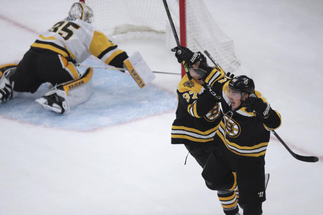 Boston Bruins center Brad Marchand, right, leaps after his winning goal off Pittsburgh Penguins goaltender Tristan Jarry (35) during the third period of an NHL hockey game in Boston, Monday, Nov. 4, 2019. (AP Photo/Charles Krupa)