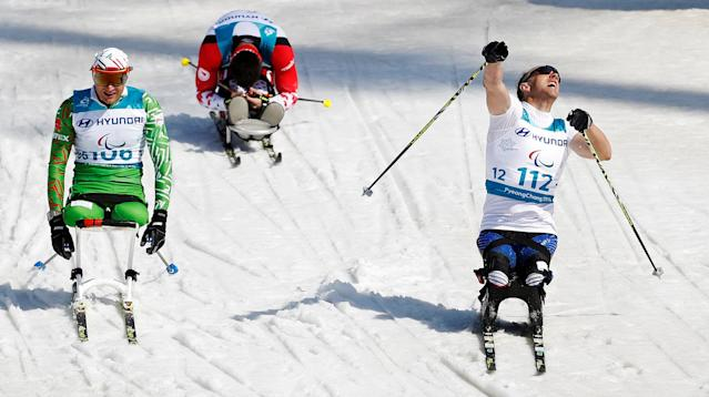 Cross-Country Skiing - Pyeongchang 2018 Winter Paralympics - Men's 1.1km Sprint - Sitting - Final - Alpensia Biathlon Centre - Pyeongchang, South Korea - March 14, 2018 - Andrew Soule (R) of the U.S. celebrates winning the gold, ahead of Dzmitry Loban (L) of Belarus and Collin Cameron of Canada. REUTERS/Carl Recine