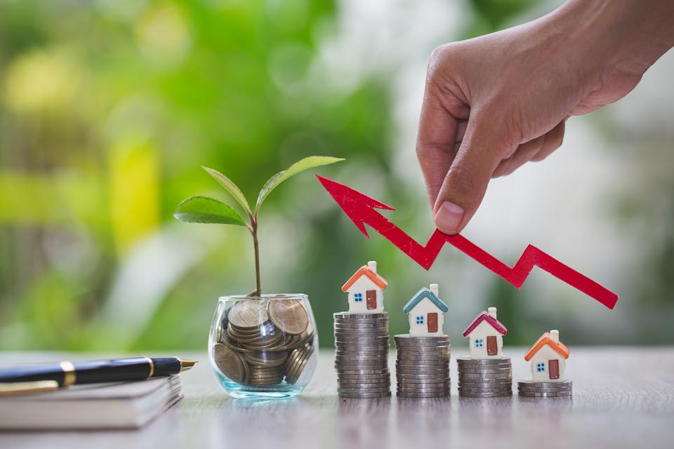 Businessperson's Hand Holding Arrow Over Stacked Coins With House Models. Home model and arrow graph with growing. Business investment the real estate concept. Fund of real estate concept.