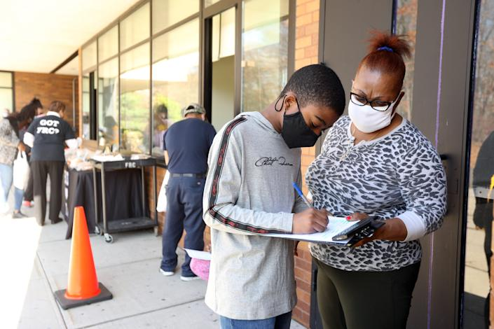 Seventh grader Lensky Jean-Pierre, 12, and his mother, Gisele, fill out paperwork to receive a Chromebook on Nov. 10 at Chestnut Ridge Middle School in New York. Jean-Pierre had been using his mother's phone for his school work and was hopeful the Chromebook would make it easier to do his work.
